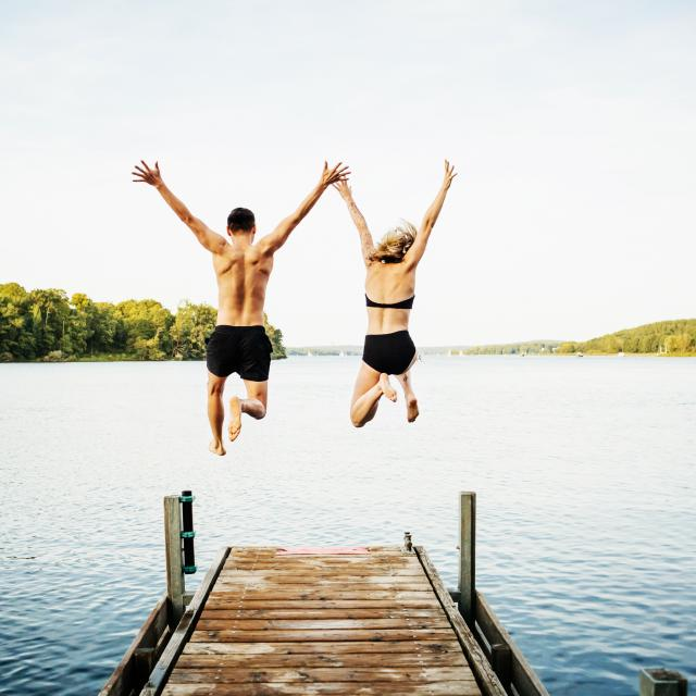 Two friends jumping with their arms in the air off the end of a jetty at a lake together.